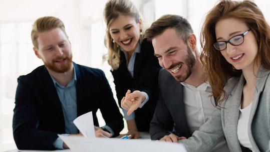 Groupe de 4 professionnels assis à une table et qui sourient en regardant des documents papier