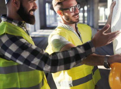 Deux jeunes hommes habillés avec des dossards de construction regardent un plan dans un bâtiment de bétons